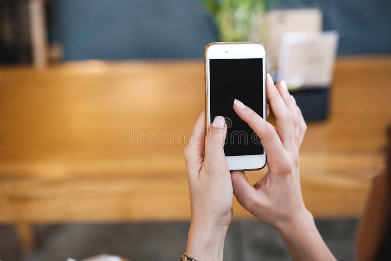 电话在女孩的手上 空的电话屏幕和查寻应用或信息关于互联网 免版税库存图片