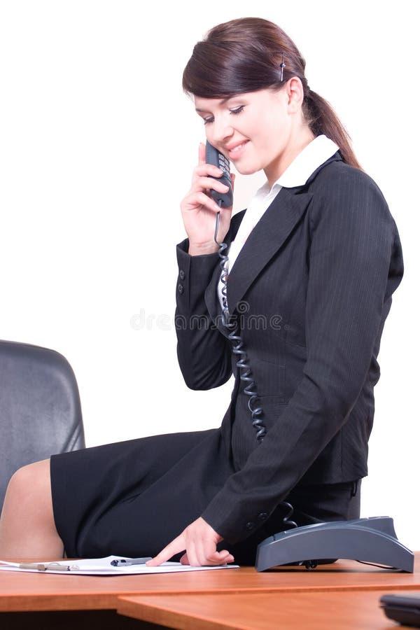 电话坐的女孩告诉表 库存图片