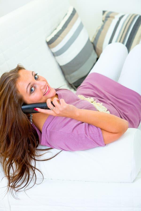 电话坐的微笑的沙发联系的妇女 免版税库存图片
