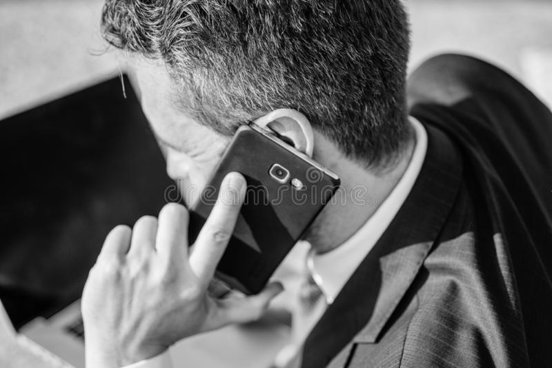 电话技术支持服务 商人在耳朵关闭附近停滞智能手机 人正装电话支持一会儿工作 库存图片