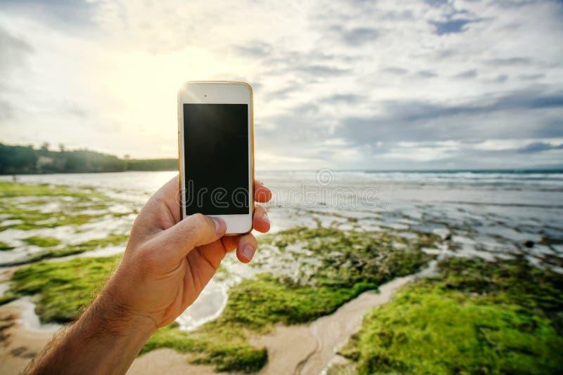 电话是一个智能手机在一个人的手上有一个空的黑屏幕的在海洋岸和阳光的背景 库存图片