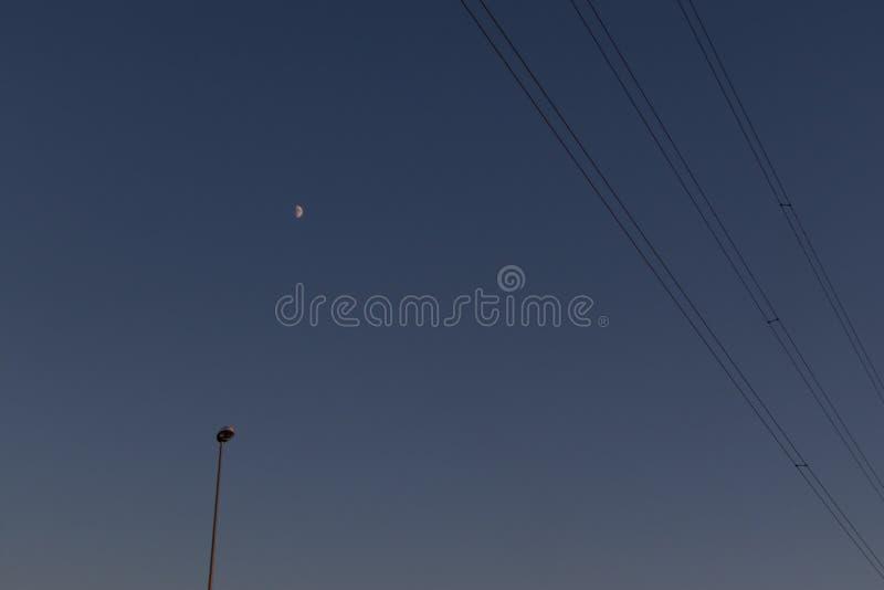 电话电缆、街灯和月亮在背景中 图库摄影