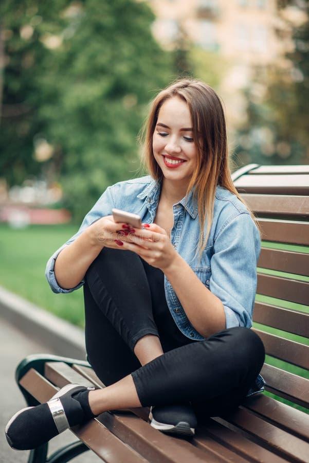 电话瘾,使用智能手机的上瘾者妇女 免版税图库摄影