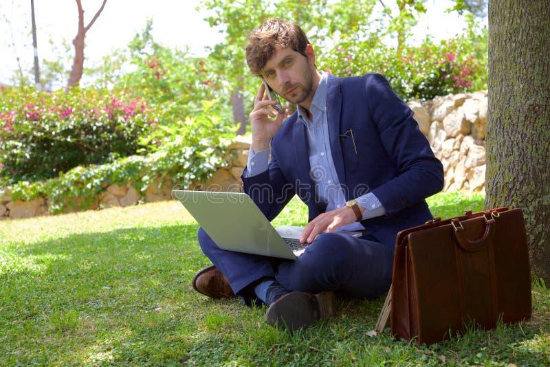 电话的严肃的商人,当与个人计算机一起使用在公园时 免版税库存照片