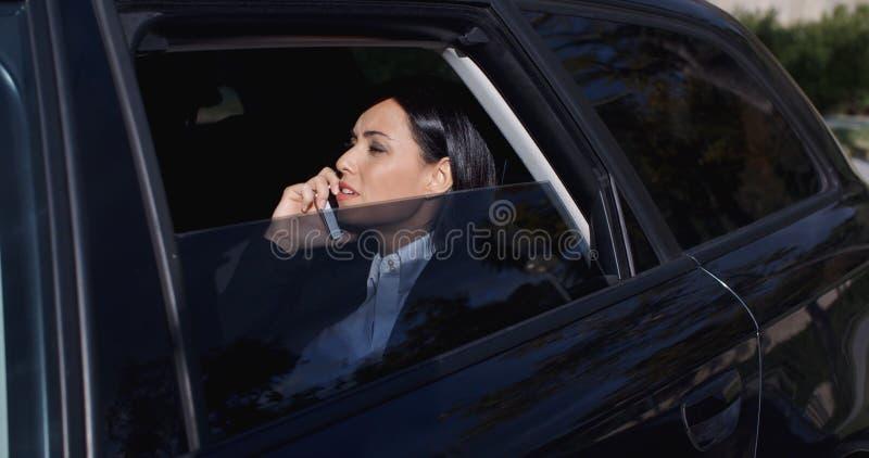 电话的严肃的年轻执行委员在大型高级轿车 免版税库存照片
