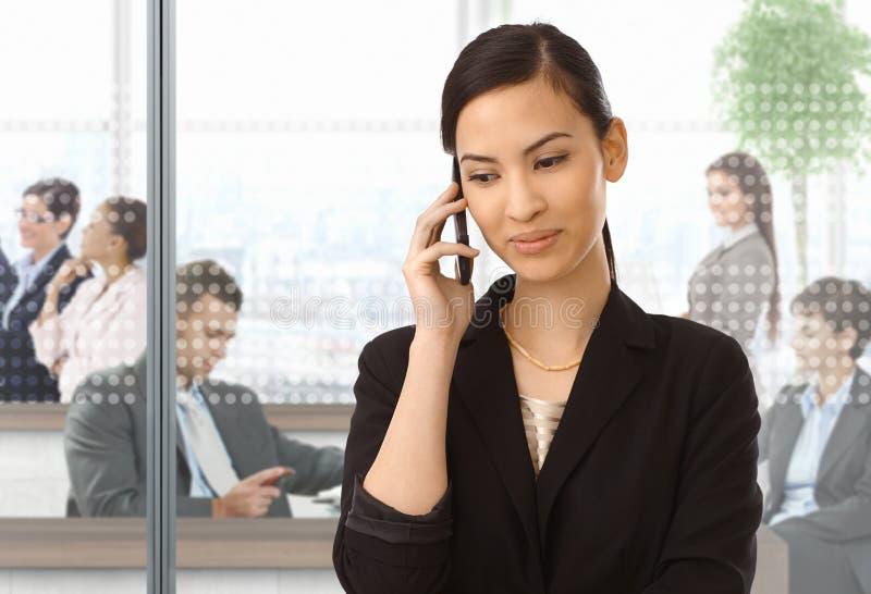 电话的亚裔女实业家在办公室 库存图片