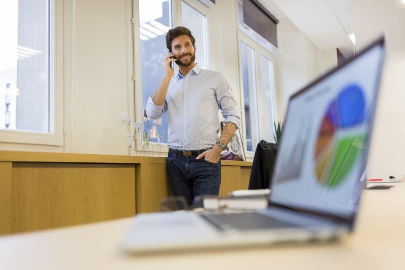 电话的人在办公室,在前景的膝上型计算机 免版税图库摄影