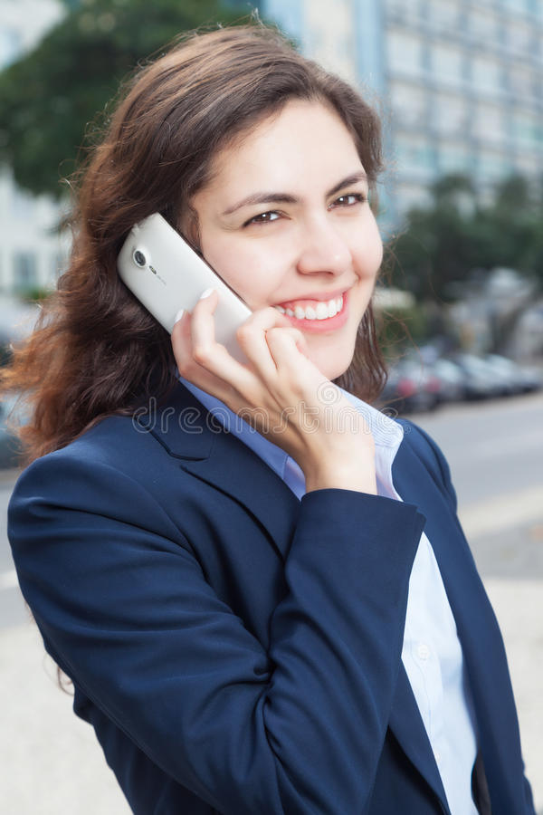 电话的可爱的女实业家在城市 免版税库存图片