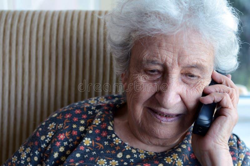 电话的可爱的高级妇女 免版税库存图片
