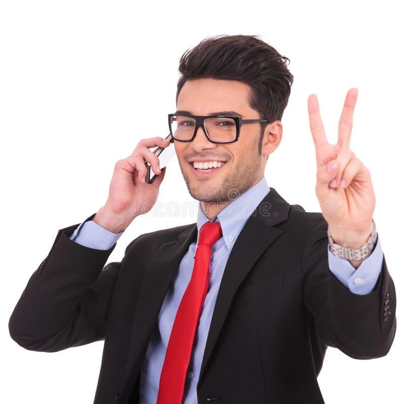 电话的商人显示胜利符号 库存照片