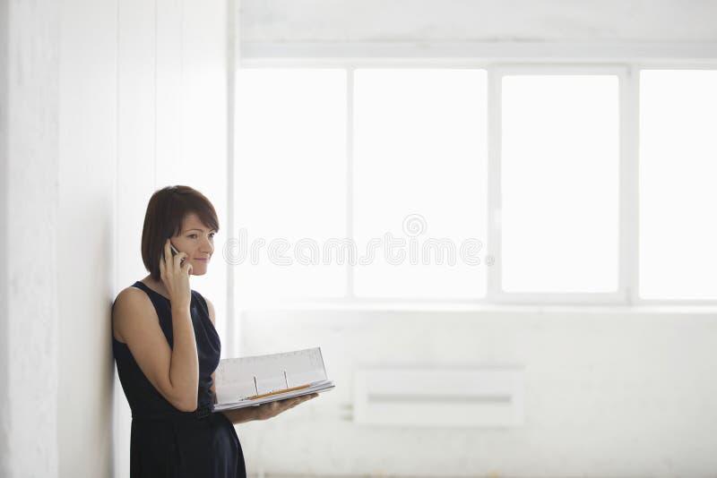 电话的女实业家,当待办卷宗时 库存图片