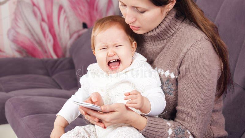 电话的妇女,忽略哭泣的孩子 库存图片