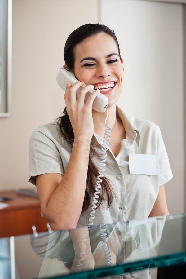 电话的愉快的女性接待员 库存照片