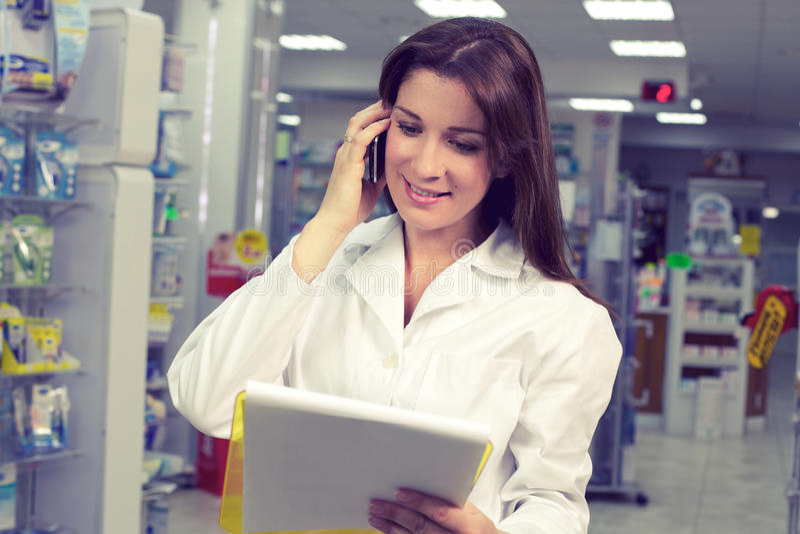 电话的愉快的女性药剂师在药房 图库摄影