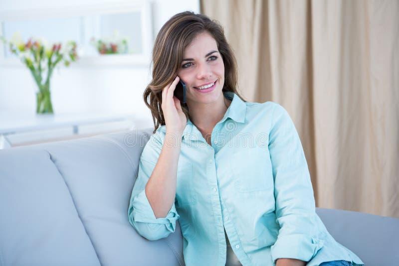 电话的愉快的妇女在长沙发 库存照片