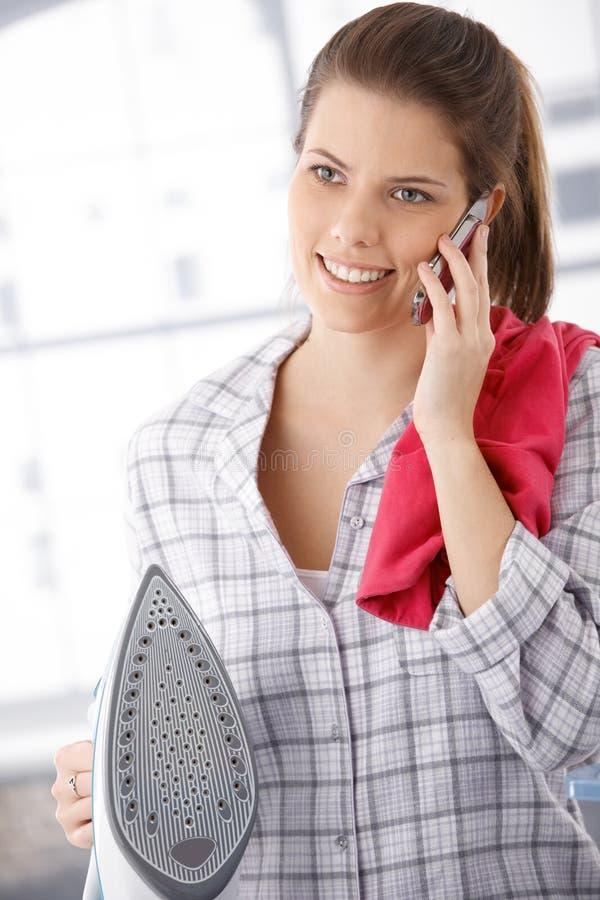 电话的愉快的妇女,执行电烙 免版税库存照片