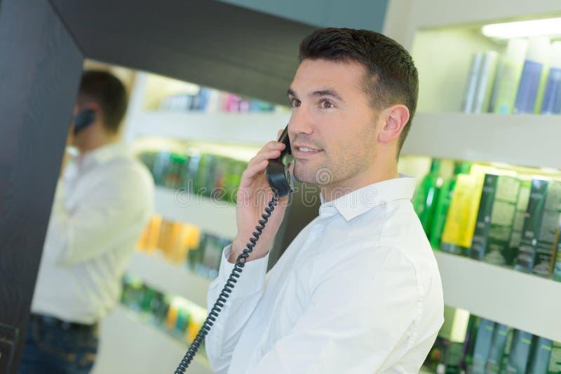 电话的英俊的hairdesser接待员有客户的 免版税库存图片