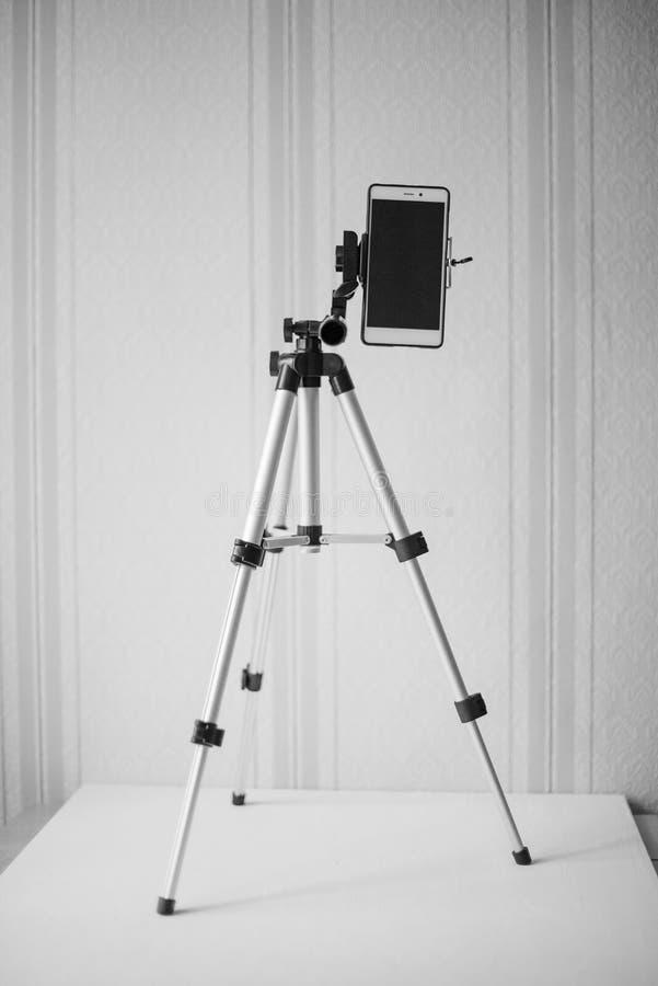 电话的辅助部件:一个智能手机的一充分地被折叠的立场在以墙纸为背景的桌上,黑和 库存图片