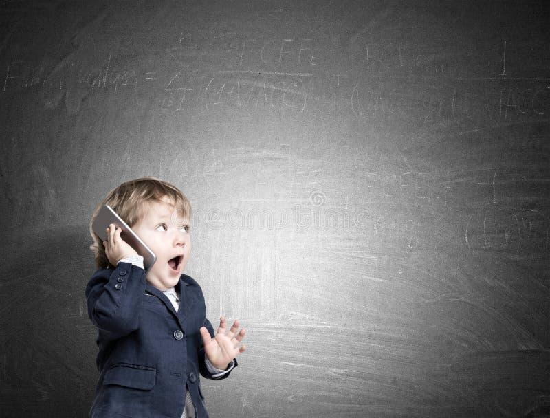 电话的逗人喜爱的小孩在黑板附近 免版税库存照片