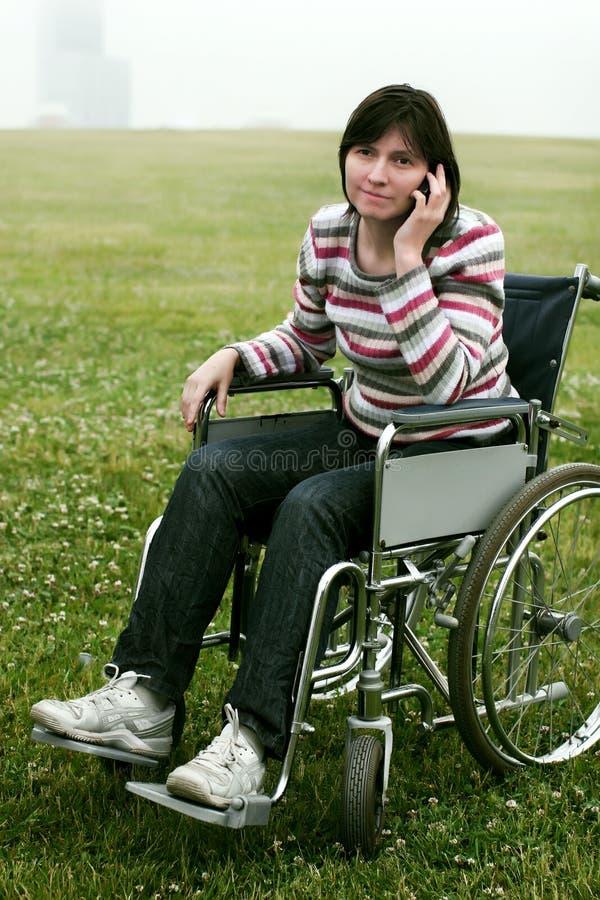 电话联系的轮椅妇女 免版税库存图片