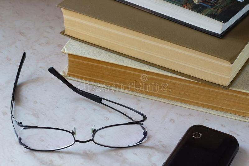 电话 玻璃和旧书在桌面上 图库摄影