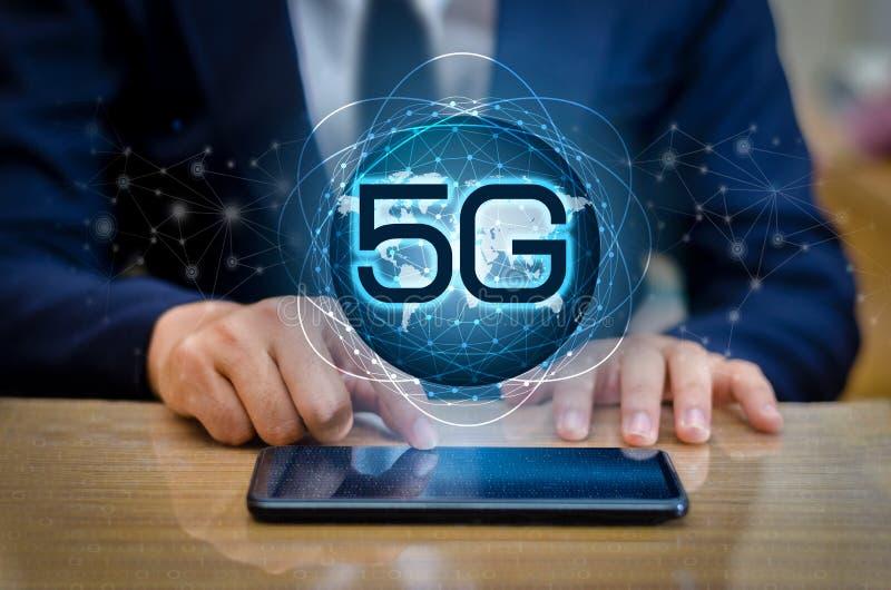 电话5g地球商人用浓缩聪明和5G的网络连接连接拿着一种空的数字式片剂的全世界侍者手 库存照片