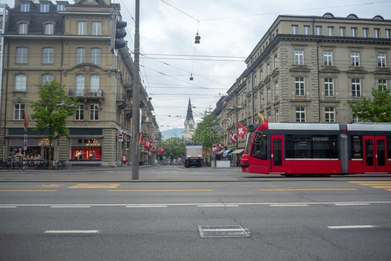 电车在伯尔尼,瑞士的首都,美丽的中世纪大厦和多云天空背景的 免版税图库摄影
