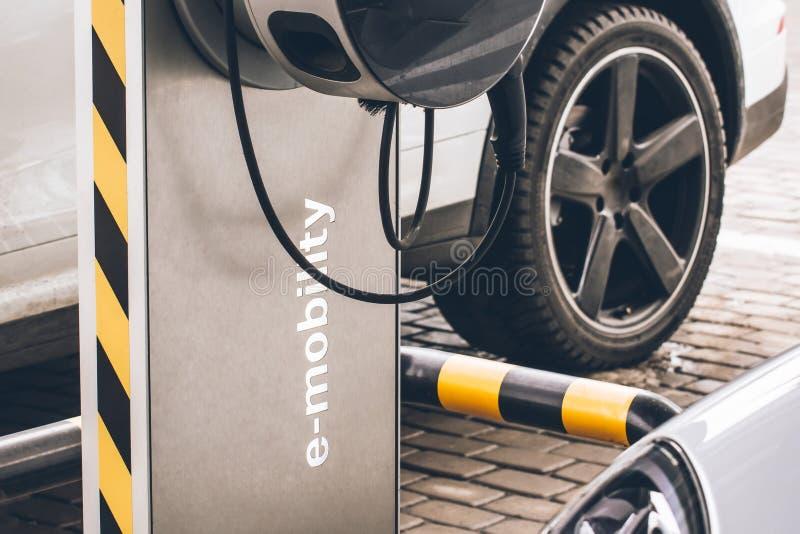 电车e流动性的在背景汽车,轮子汽车换装燃料 免版税库存照片