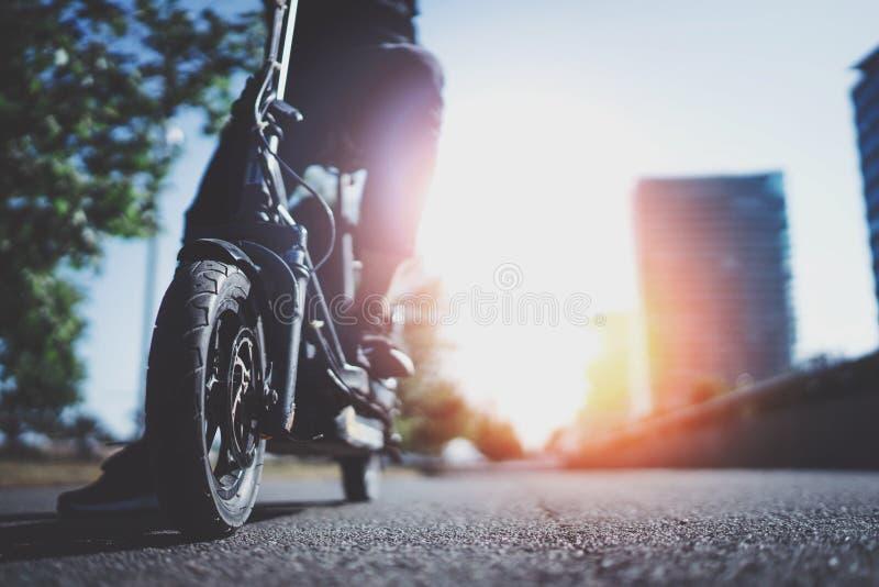 电都市运输 准备好的年轻人骑他的电滑行车自行车在城市的中心 创新 库存照片