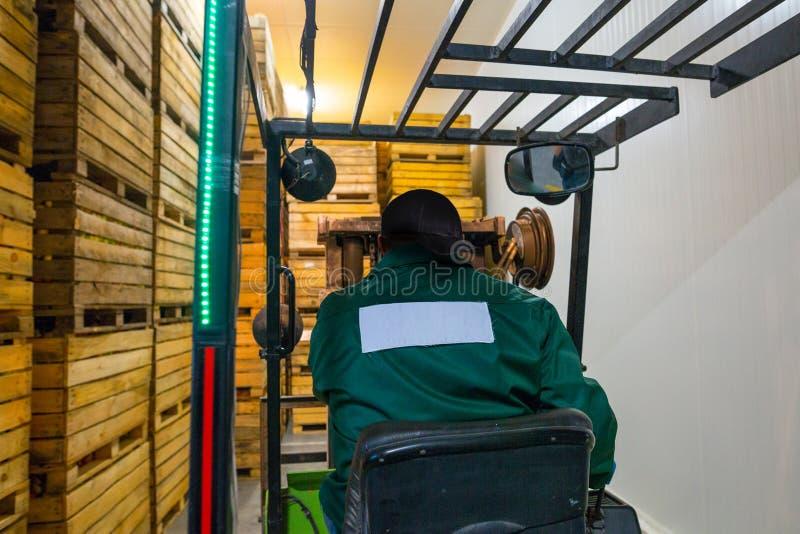 电铲车的雇员运载有r的容器 免版税图库摄影