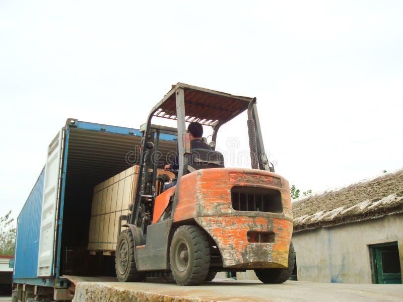 电铲车装货货物到容器里 图库摄影