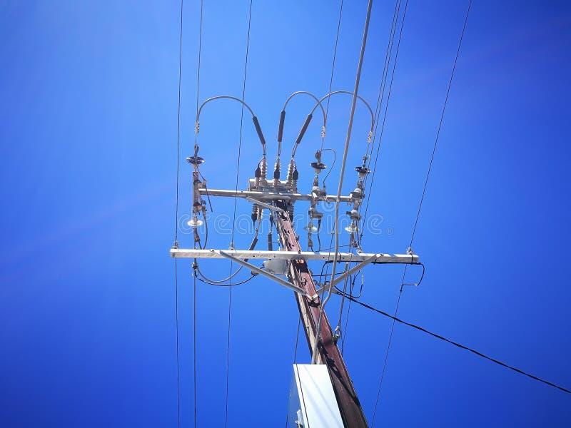 电高压变压器一个低角度视图送的输电线在天空蔚蓝背景隔绝的能量一代 免版税库存图片