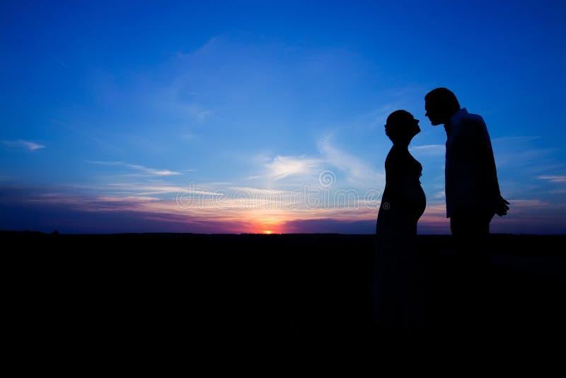 男人和一名孕妇的剪影 免版税库存照片