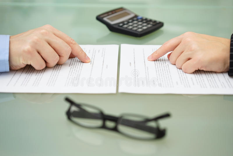 男人和和妇女慢慢地读保险单 库存照片