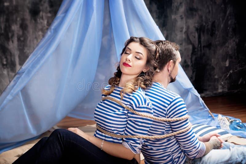 男人和妇女一起一定与绳索 概念 免版税图库摄影