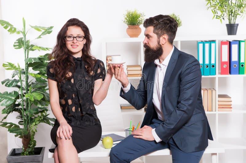 男人和妇女交谈咖啡时间 办公室谣言 办公室咖啡 夫妇工友放松咖啡休息 份额咖啡 免版税库存照片