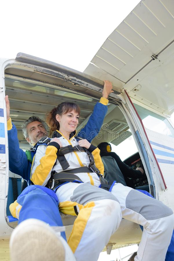 男人和妇女保持平衡从航空器跳跃 库存图片
