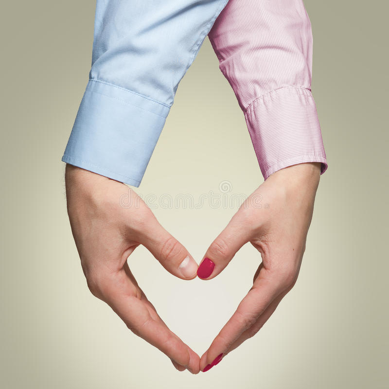 男人和妇女做形状心脏用手在黄色backg 免版税库存照片