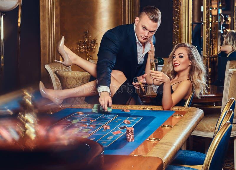 男人和妇女充当赌博娱乐场 免版税库存照片
