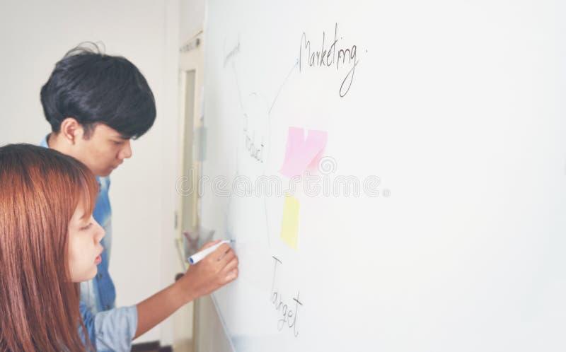 男人和妇女在一个白板写着一个计划 提出到队 计划概念通过写工作草稿  图库摄影
