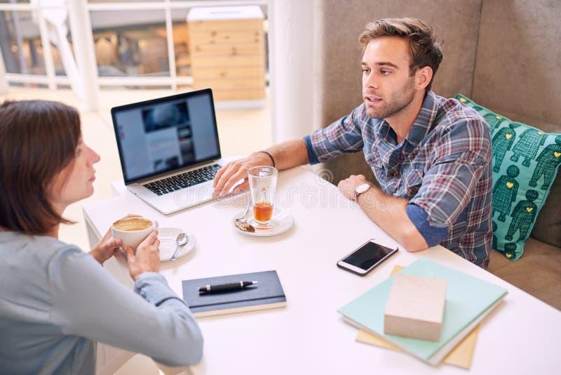 男人和妇女在地方咖啡馆的举办一个业务会议 免版税库存图片
