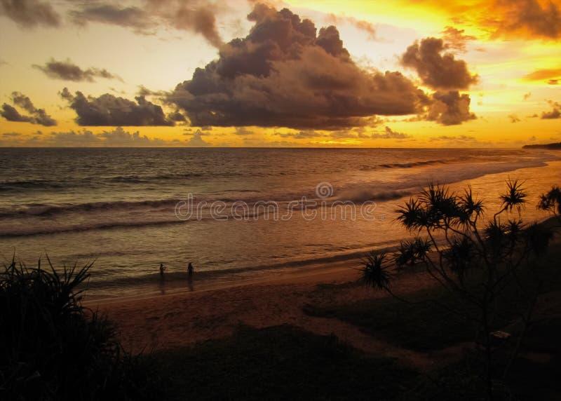 男人和妇女在日落的海洋被拍摄 免版税库存照片
