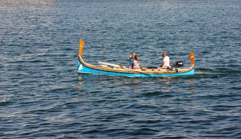 男人和妇女在有严厉上尉的传统马尔他小船游泳和采取照片 库存照片