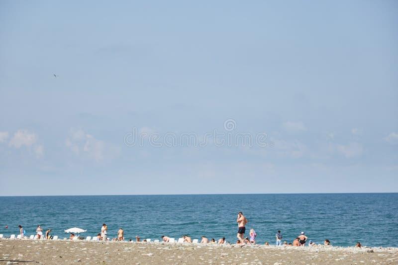 男人和妇女在海滩晒日光浴并且沐浴巴统 免版税库存图片