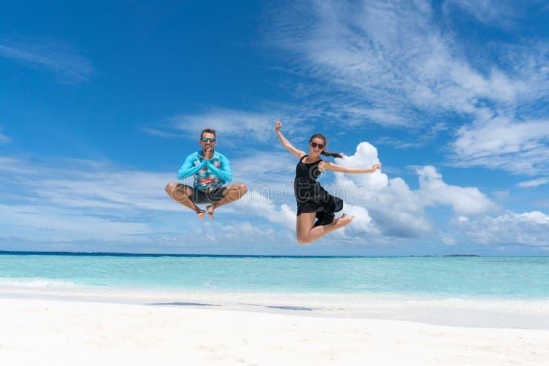 男人和妇女在海滩跳用海洋透明水在马尔代夫 免版税库存照片