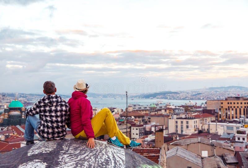 男人和妇女坐高大厦屋顶上面在晚上 免版税库存照片