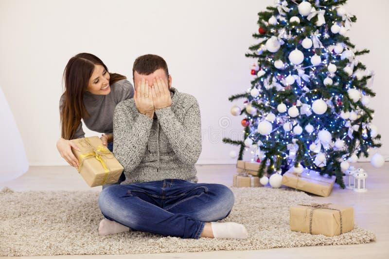 男人和妇女开放圣诞礼物在圣诞树新年 库存图片