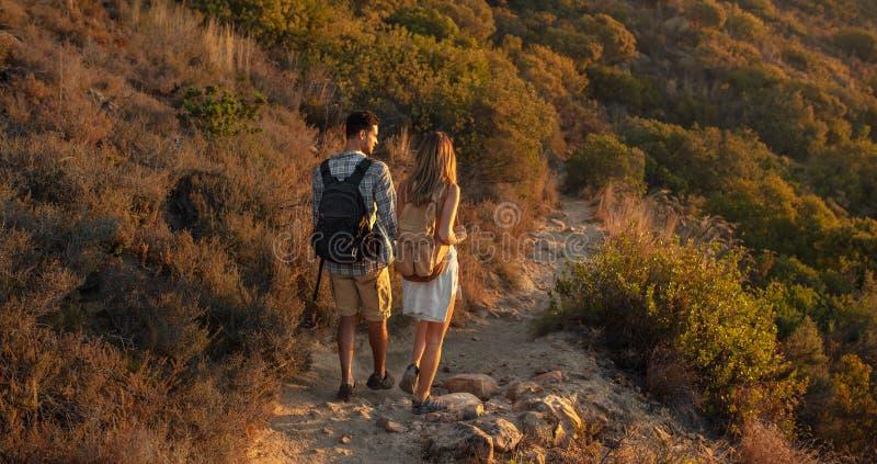 男人和妇女徒步旅行者背面图迁徙一条岩石道路的在小山边 走通过山行迹的徒步旅行者夫妇探索的自然 免版税库存照片