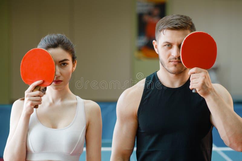 男人和妇女拿着乒乓球球拍户内 库存照片