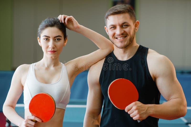 男人和妇女拿着乒乓球球拍户内 免版税库存照片
